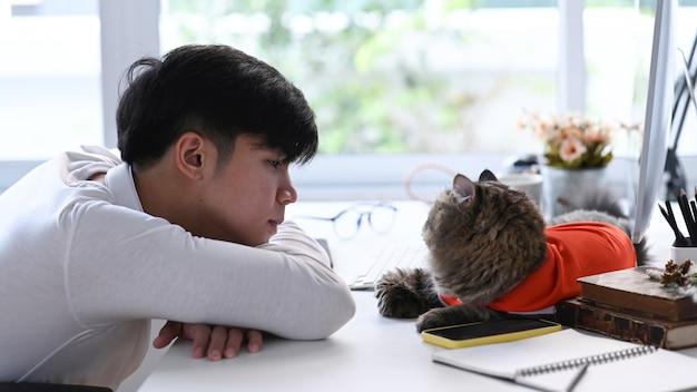 Junger asiatischer mann, der auf weißem schreibtisch mit seiner katze zu hause liegt
