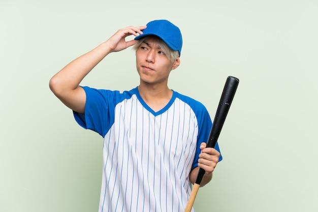 Junger asiatischer mann, der baseball über dem lokalisierten grün hat zweifel und mit spielt, verwirren gesichtsausdruck