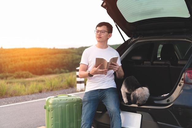 Junger asiatischer mann, der buch hält und front beim sitzen im offenen stamm des autos mit hunden betrachtet.