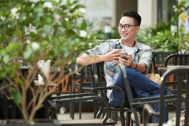 Junger asiatischer mann, der café am im freien mit smartphone und tee sich entspannt