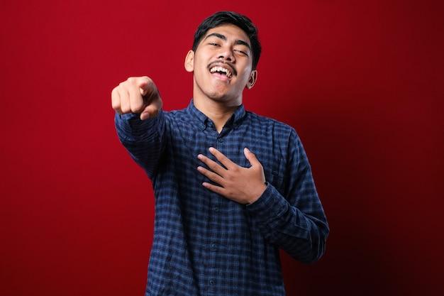 Junger asiatischer mann, der ein lässiges hemd über rotem hintergrund trägt und dich auslacht, mit dem finger auf die kamera mit der hand über den körper zeigt, schamausdruck