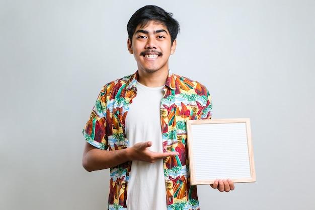 Junger asiatischer mann, der ein leeres briefbrett hält, das mit dem finger auf die kamera und auf dich zeigt, handzeichen, positive und selbstbewusste geste von vorne
