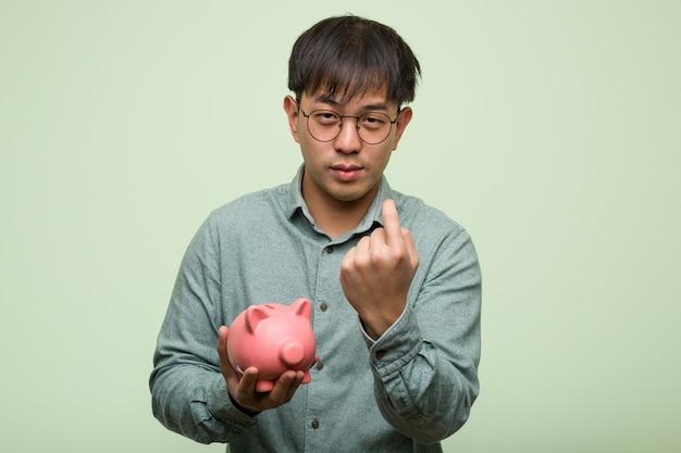 Junger asiatischer mann, der ein sparschwein einlädt zu kommen hält