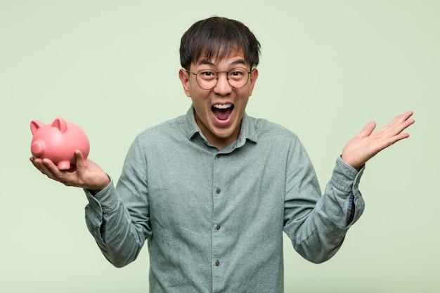 Junger asiatischer mann, der ein sparschwein feiert einen sieg oder einen erfolg hält
