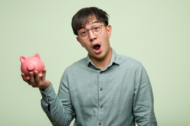 Junger asiatischer mann, der ein sparschwein hält etwas auf palmenhand hält