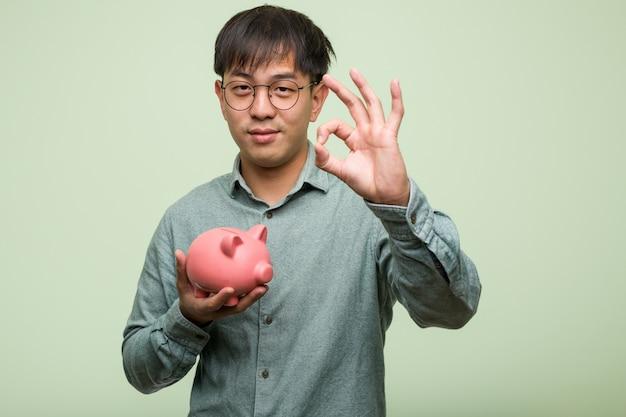 Junger asiatischer mann, der ein sparschwein nett und überzeugt hält, okaygeste tuend