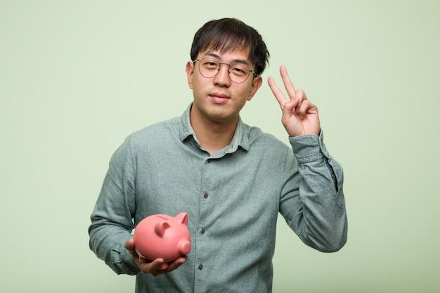 Junger asiatischer mann, der ein sparschwein zeigt nummer zwei hält