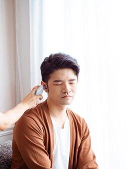 Junger asiatischer mann, der eine chirurgische maske trägt und ein ohrthermometer verwendet