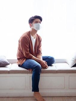 Junger asiatischer mann, der eine hygienische maske trägt, um eine infektion in der häuslichen quarantäne zu verhindern