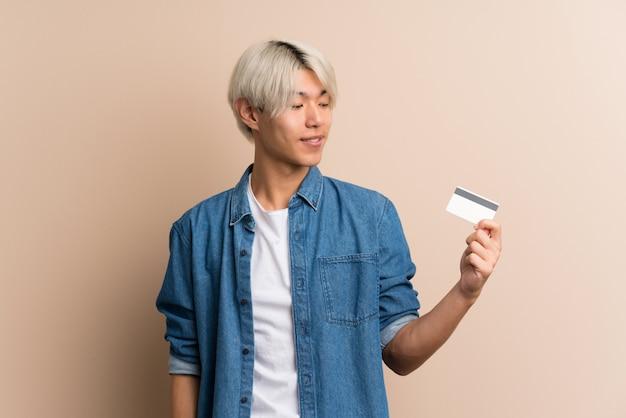 Junger asiatischer mann, der eine kreditkarte hält