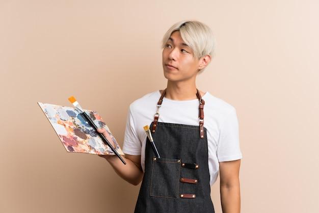 Junger asiatischer mann, der eine palette hält und eine idee denkt