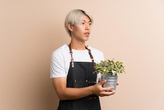 Junger asiatischer mann, der einen blumentopf nimmt