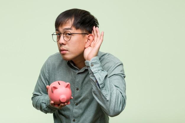Junger asiatischer mann, der einen sparschweinversuch zum hören eines klatsches hält