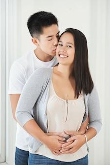 Junger asiatischer mann, der freundin auf backe umarmt und küsst