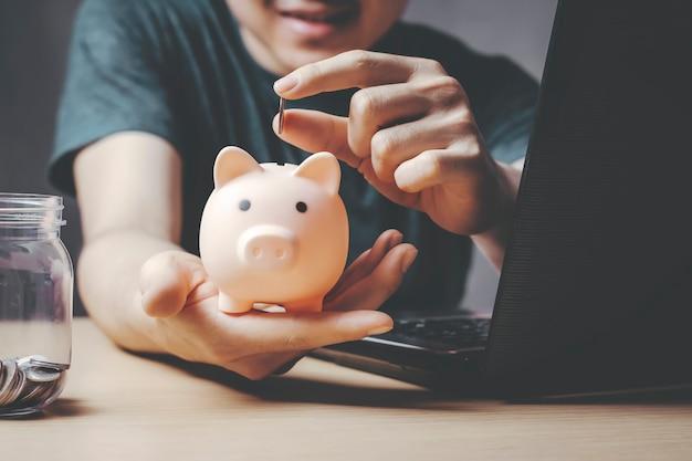 Junger asiatischer mann, der geldmünze in das sparschwein trägt glücklich sein mit geld sparen und geld sparen.