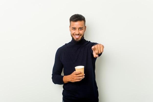 Junger asiatischer mann der gemischten rasse, der ein fröhliches lächeln des kaffee zum mitnehmen hält, zeigt nach vorne.