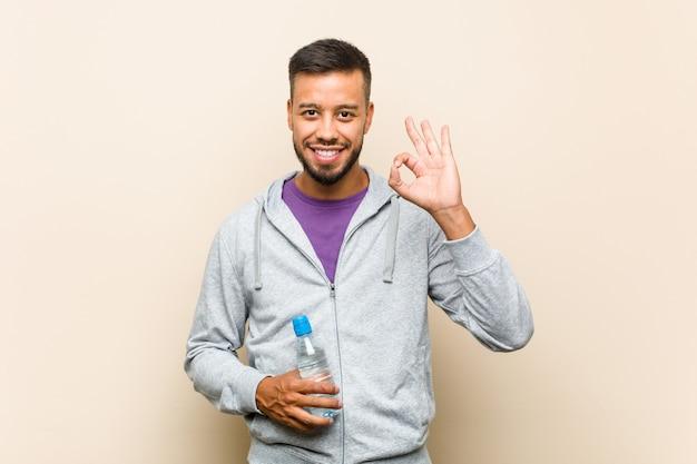 Junger asiatischer mann der gemischten rasse, der eine wasserflasche fröhlich und zuversichtlich hält, die ok geste zeigt.