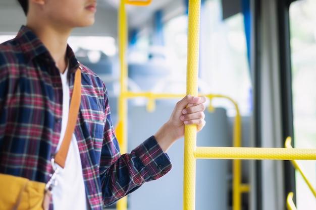 Junger asiatischer mann, der griff auf dem öffentlichen bus hält