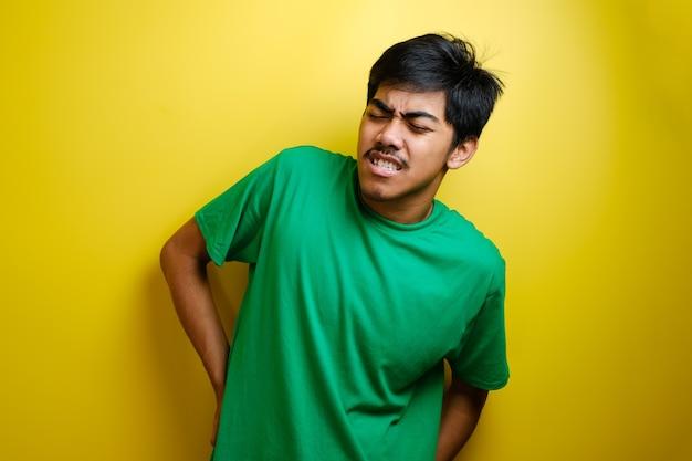 Junger asiatischer mann, der grünes t-shirt trägt und schmerzen im unteren rücken hat, seinen rücken reibt, erschöpftes konzept. gelber hintergrund
