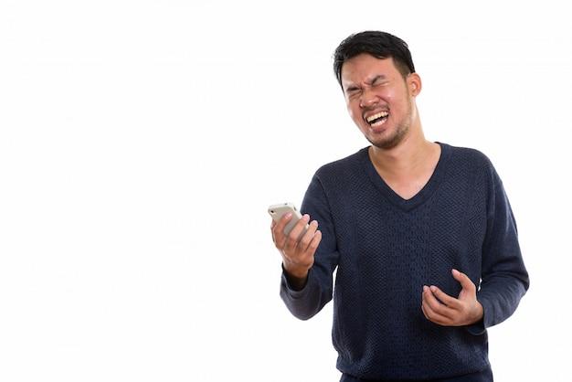 Junger asiatischer mann, der handy hält und besorgt aussieht