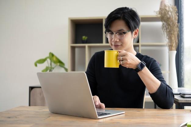 Junger asiatischer mann, der heißen kaffee trinkt und nachrichten auf laptop-computer überprüft.