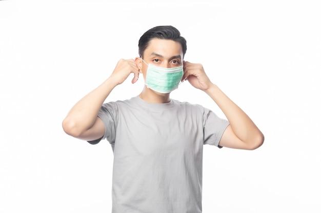 Junger asiatischer mann, der hygienemaske trägt, um infektion, 2019-ncov oder coronavirus zu verhindern. atemwegserkrankungen in der luft wie pm 2.5-kämpfe und grippe. studioaufnahme isoliert auf weiß
