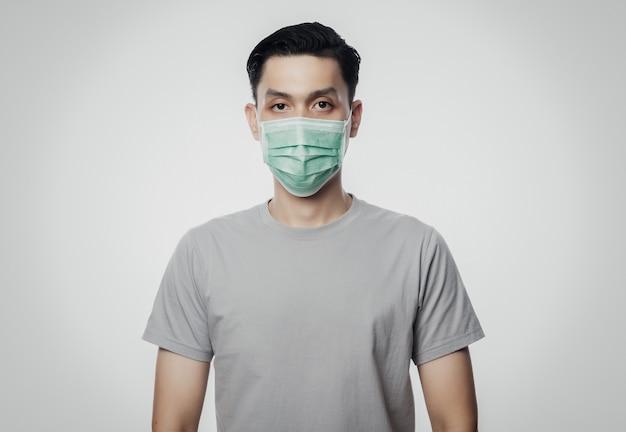Junger asiatischer mann, der hygienemaske trägt, um infektion, 2019-ncov oder coronavirus zu verhindern. atemwegserkrankungen in der luft wie pm 2.5-kämpfe und grippe. studioaufnahme lokalisiert auf weißer wand