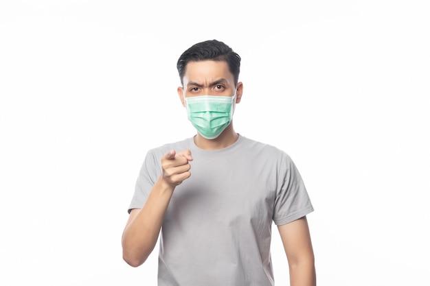 Junger asiatischer mann, der hygienemaske trägt und auf kamera mit zweifelsgesicht, 2019-ncov oder coronavirus zeigt. atemwegserkrankungen in der luft wie pm 2.5-kämpfe und isolierte grippe