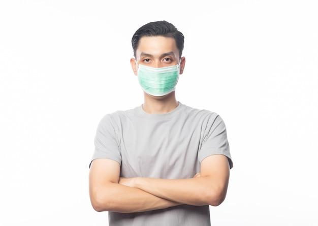 Junger asiatischer mann, der hygienemaske und verschränkte arme trägt, um infektion, 2019-ncov oder coronavirus zu verhindern. atemwegserkrankungen in der luft wie pm 2.5-kämpfe und grippe. isoliert