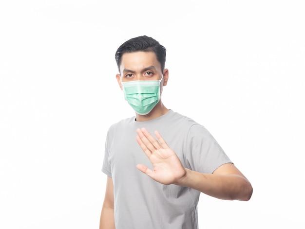 Junger asiatischer mann, der hygienemasken gestikulierende stopps trägt, um infektion, 2019-ncov oder coronavirus zu verhindern. atemwegserkrankungen in der luft wie pm 2.5-kämpfe und isolierte grippe