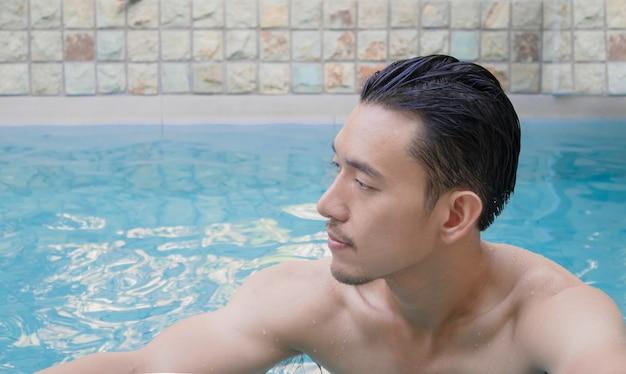 Junger asiatischer mann, der im schwimmbad im urlaub steht.