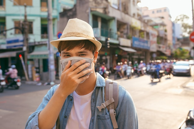 Junger asiatischer mann, der in der stadt mit verschmutzter luft lebt