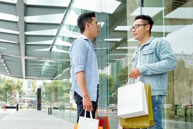 Junger asiatischer mann, der in der straße steht und verkäufe und schnäppchen während des schwarzen freitags bespricht