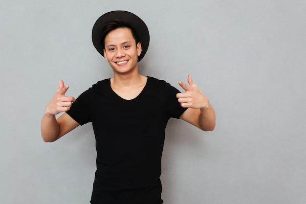 Junger asiatischer mann, der isoliert steht und zeigt.