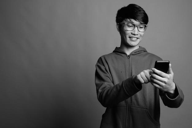 Junger asiatischer mann, der jacke mit brille trägt