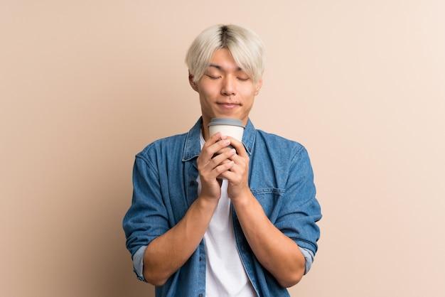 Junger asiatischer mann, der kaffee hält, um wegzunehmen
