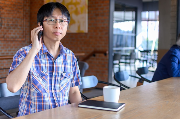 Junger asiatischer mann, der kaffee im café trinkt und smartphone verwendet
