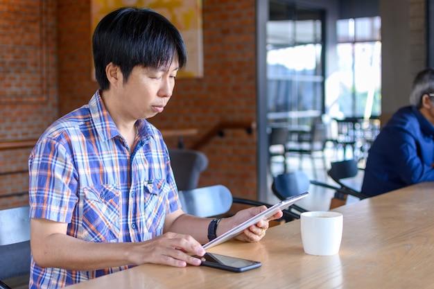 Junger asiatischer mann, der kaffee im café trinkt und tablet-computer verwendet