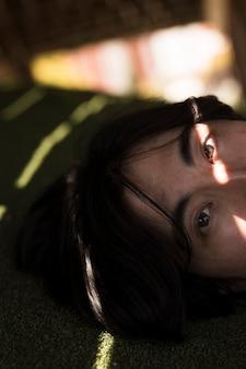 Junger asiatischer mann, der kamera im schatten betrachtet