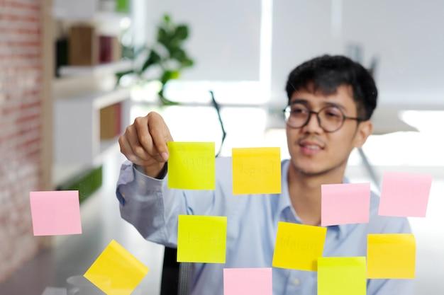 Junger asiatischer mann, der klebrige anmerkung über glaswand im büro, geschäft gedanklich löst kreative ideen, bürolebensstil, erfolg im geschäft liest