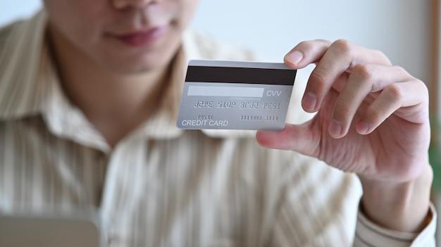 Junger asiatischer mann, der kreditkarte für online-banking oder online-shopping hält.