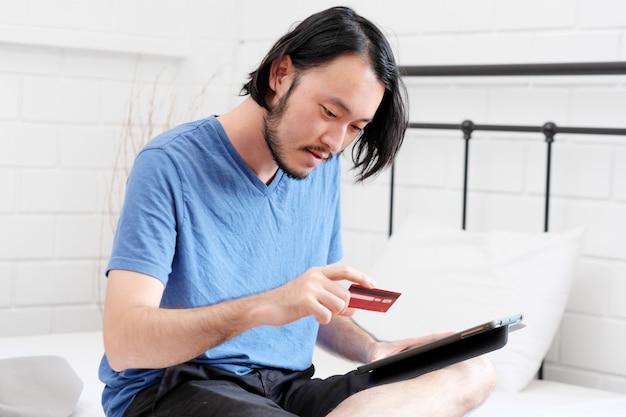 Junger asiatischer mann, der kreditkarte hält und digitale tablette für online zu hause kaufen, geschäfts- und technologiekonzept, digitales marketing, zufälliger lebensstil verwendet