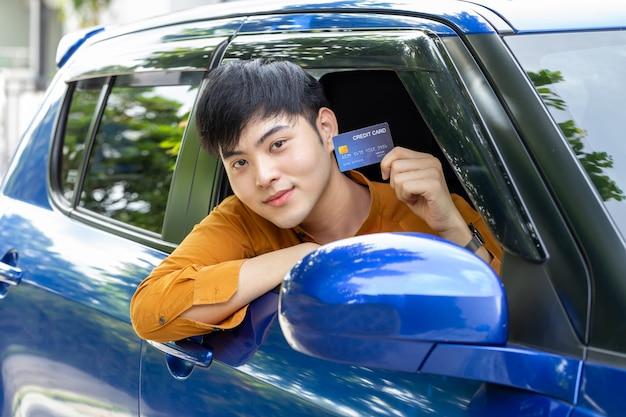 Junger asiatischer mann, der kreditkarte hält und im auto sitzt.