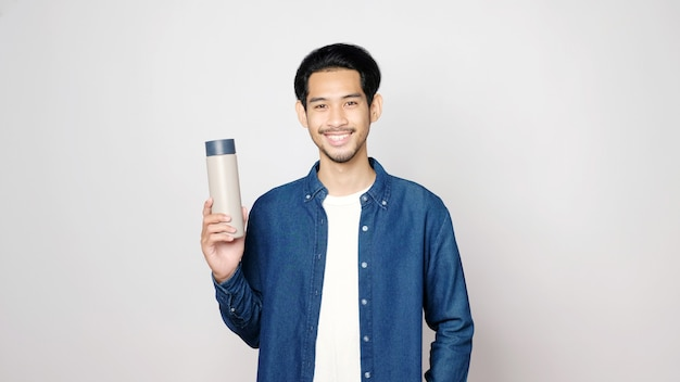 Junger asiatischer mann, der lächelnd und wiederverwendbare flasche hält