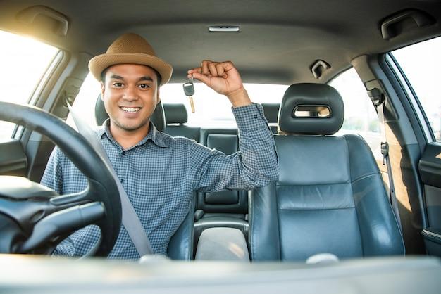 Junger asiatischer mann, der lächelt und einen schlüssel in seinem auto zeigt.
