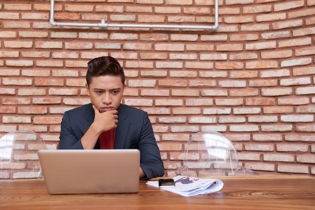 Junger asiatischer mann, der laptopschirm betrachtet und sein kinn reibt