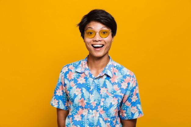 Junger asiatischer mann, der lokal über gelbem raum aufwirft.