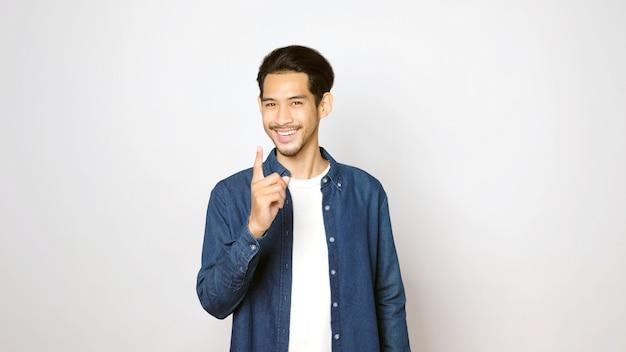 Junger asiatischer mann, der mit dem finger zeigt, lächelt und in die kamera schaut, während er über isoliertem grauem hintergrund mit kopienraum, banner, asien-typ in positivem ausdruck steht