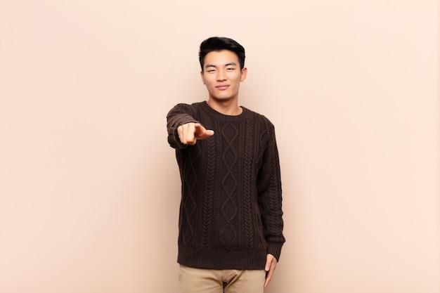Junger asiatischer mann, der mit einem zufriedenen, selbstbewussten, freundlichen lächeln auf kamera zeigt und sie über farbwand wählt