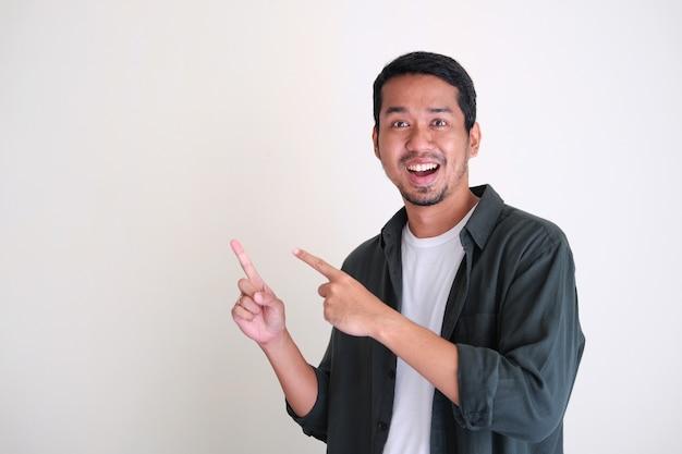 Junger asiatischer mann, der mit glücklichem gesichtsausdruck auf seine seite zeigt